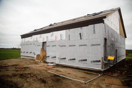 Weatherproofing material partially covers what Krystal and Rusty Armstrong were hoping to call their dream home on Wednesday, Oct. 10, 2018, south of Indianola. They say contractor Dave Daughenbaugh has taken their money for work to be done but has walked off the job and left them with a shell of a building.