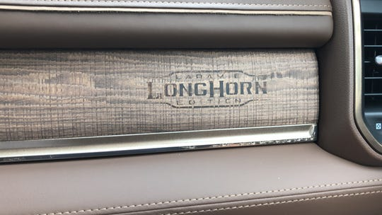 The 2019 Ram 1500 pickup's interior features unique touches like a hand-branded badge on the dashboard.