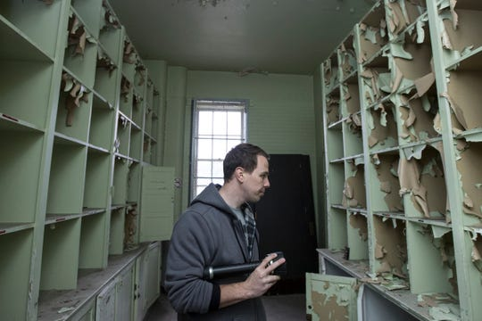 Jeff Adkins, co-founder of Detroit Paranormal Expeditions checks out a clothes storage room on the third floor at the Kay Beard Building in Westland, Friday, October 12, 2018.