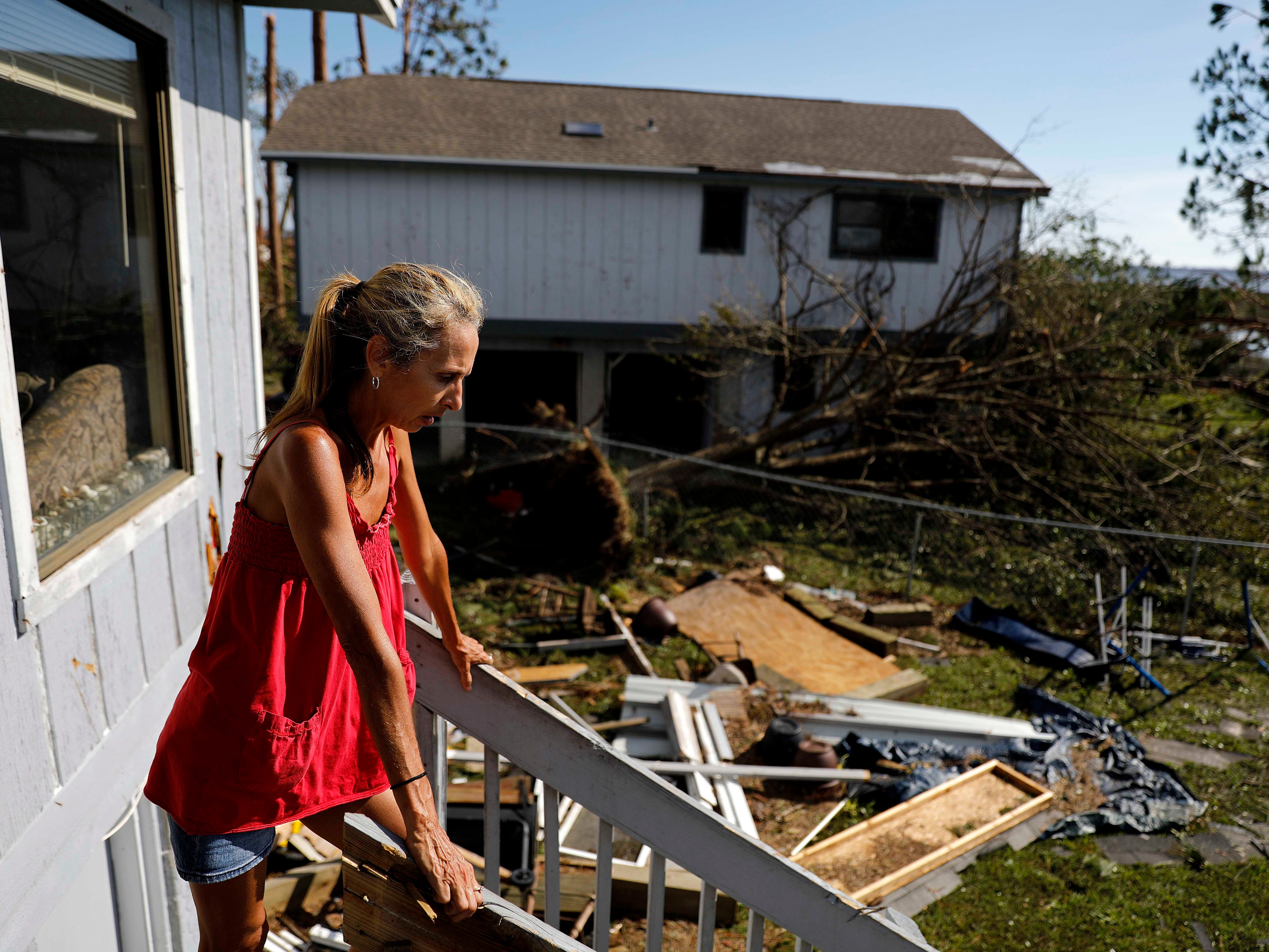 "Monica Jones looks out over the debris littering her yard after riding out hurricane Michael in her home in Callaway, Fla., Thursday, Oct. 11, 2018. ""I didn't think it was going to be this bad,"" said Jones on her decision to stay through the storm. The devastation inflicted by Hurricane Michael came into focus Thursday with rows upon rows of homes found smashed to pieces, and rescue crews began making their way into the stricken areas in hopes of accounting for hundreds of people who may have stayed behind."