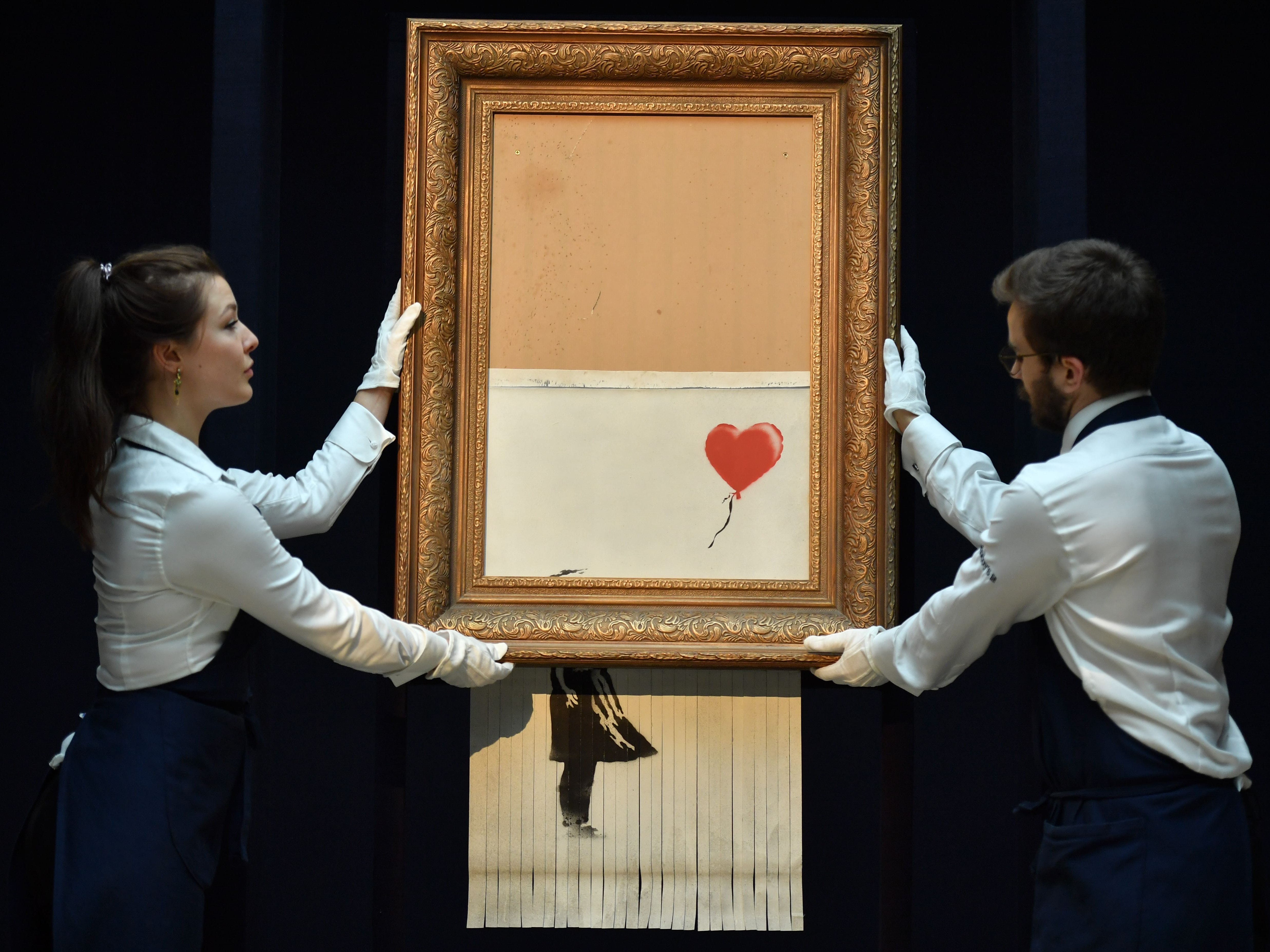 "Sotheby's employees pose with the newly completed work by artist Banksy entitled ""Love is in the Bin"", a work that was created when the painting ""Girl with Balloon"" was passed through a shredder in a surprise intervention by the artist, at Sotheby's auction house in London on Oct. 12, 2018, following the work's sale. - The buyer of a work by street artist Banksy that was partially destroyed moments after it sold has gone through with the purchase, Sotheby's auction house said on October 11, 2018. The painting ""Girl with Balloon"" was passed through a shredder hidden in the frame just after it went under the hammer last week for £1,042,000 ($1.4 million, 1.2 million euros). The modified version has now been certified by Banksy's authentication body Pest Control as a new piece of work in its own right, entitled ""Love is in the Bin""."
