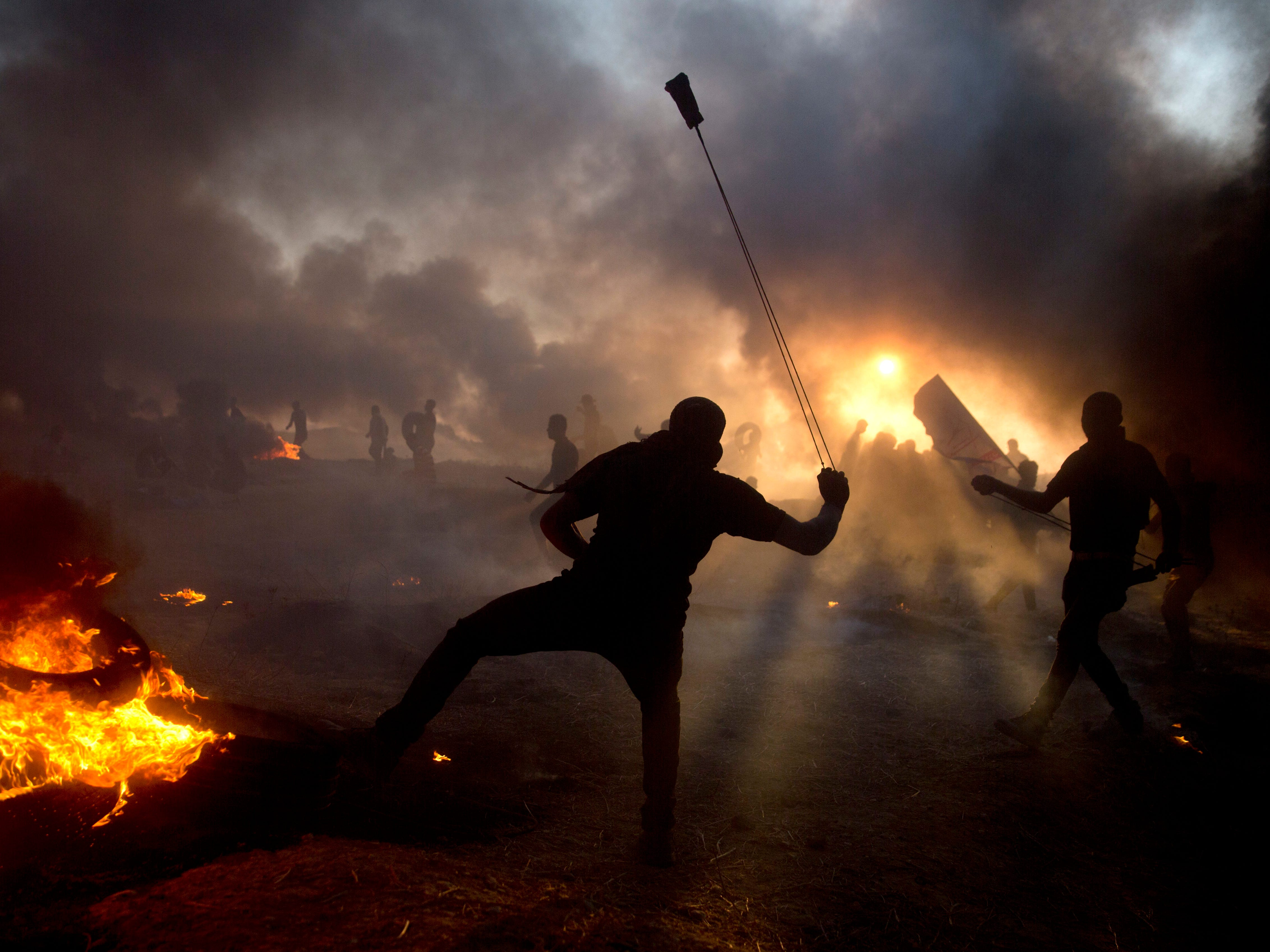 Black smoke from burning tires covers the sky as Palestinian protesters hurl stones toward Israeli troops during a protest at the Gaza Strip's border with Israel, Friday, Oct. 12, 2018.