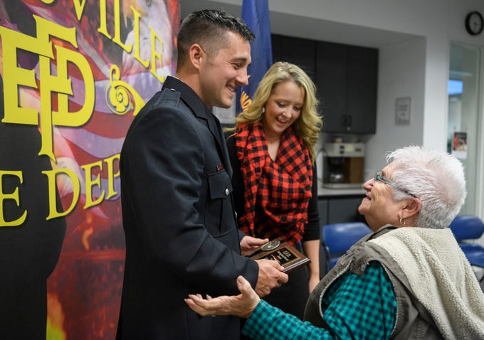 """New Evansville Firefighter Ryan Lux, left, receives well wishes from his Aunt Nancy Shockley, right, and his fiancé Jessica Schmitt, back center, before posing for a picture together after his graduation ceremony at the American Red Cross Headquarters in Evansville, Ind., Friday, Oct. 12, 2018. """"I am so proud of him. I was overwhelmed with emotion, I immediately started bawling,"""" Schmitt said of him being named the Distinguished Recruit of his class."""