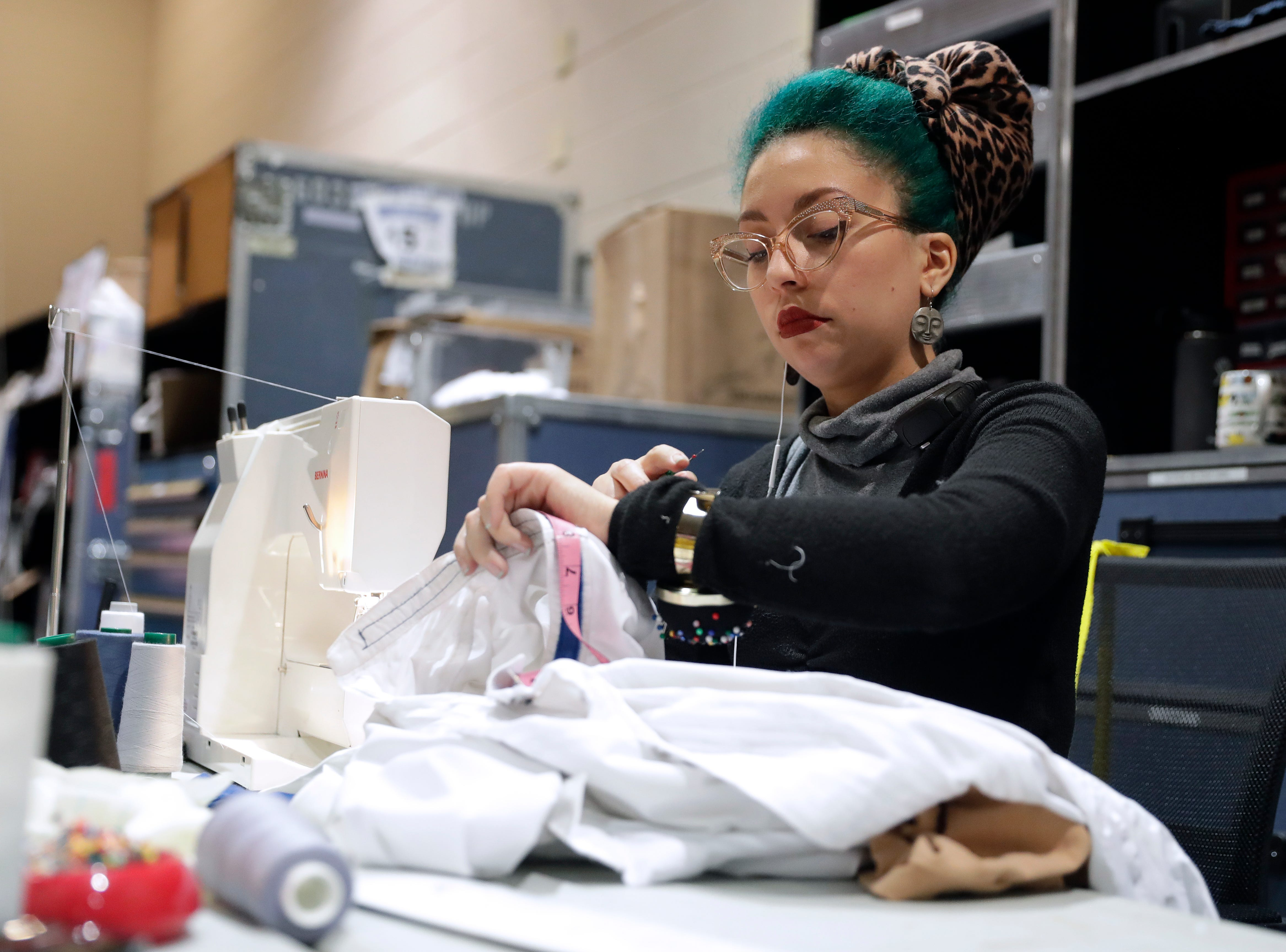 """Wardrobe technician Franchesca Alicea makes adjustments to a costume before the start of a six-show run of Cirque de Soleil's """"Crystal"""" at the Resch Center in Ashwaubenon, Wis."""