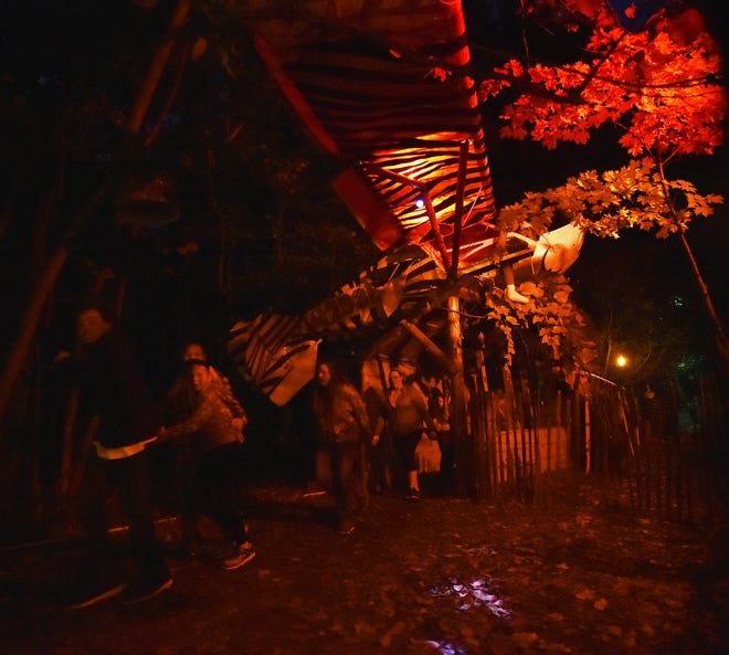 Haunted Mansion guests navigate their way under a fiery crashed airplane on the haunted trail leading to the mansion.