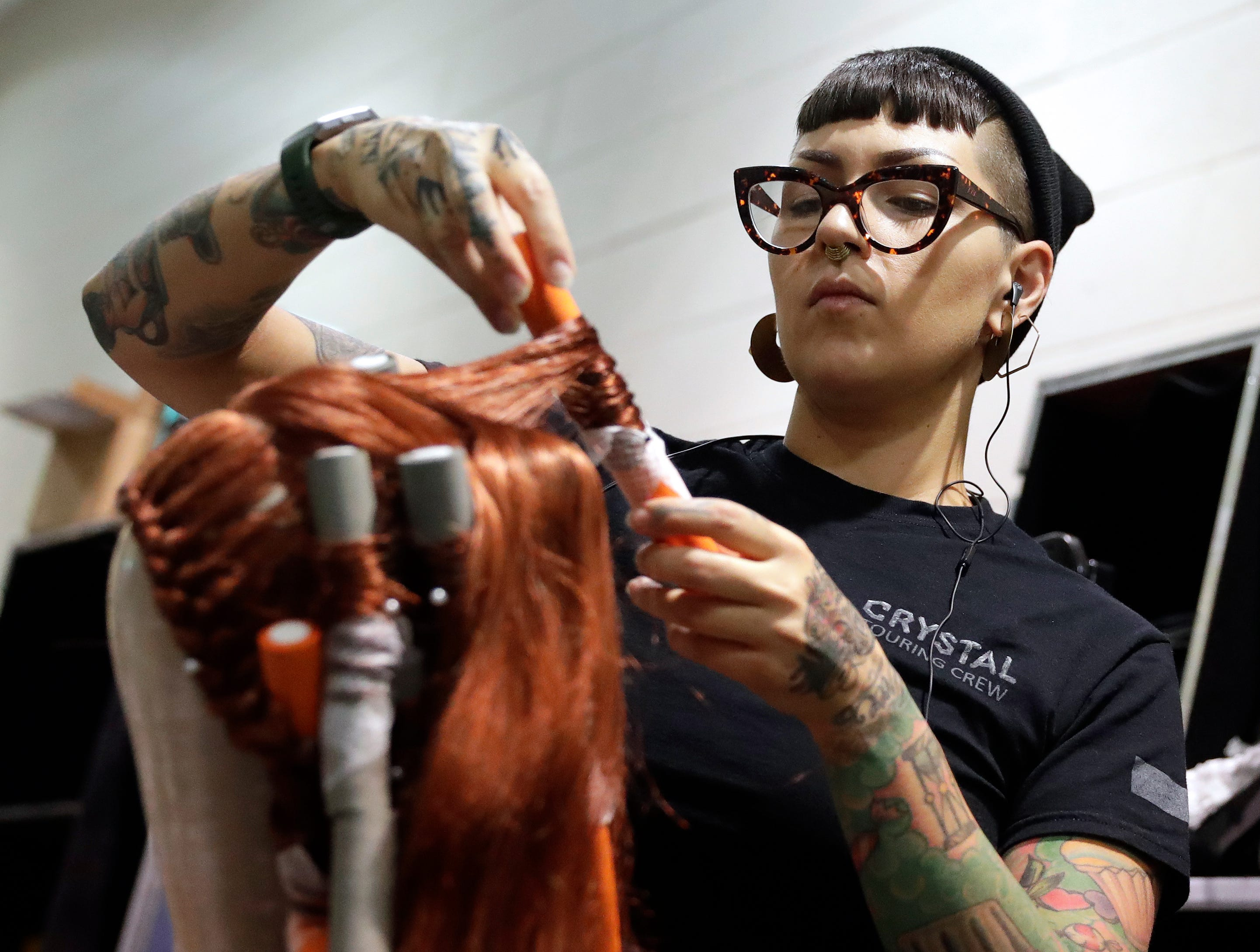 """Kate Major, wardrobe technician for Cirque du Soleil's """"Crystal"""", styles a wig before the first performance Oct. 11, 2018 at the Resch Center in Ashwaubenon, Wis."""