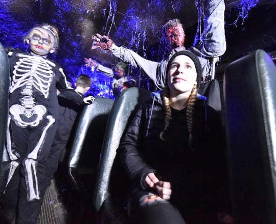 Morgan Schraeder of Sturgeon Bay is surrounded as she rides the Zombie Bus from the dark corn maze to the Haunted Mansion.