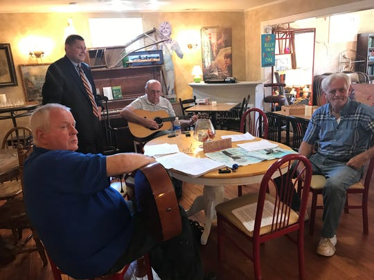 Lucas Marchant, a petition candidate for 13th Circuit Solicitor, visits with voters Hugh Hughes, Don Ballenger and John Rayley as they practice songs at My  Sister's Store Books & More in Travelers Rest.