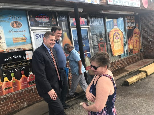 Lucas Marchant, a petition candidate for 13th Circuit Solicitor, left, and supporter, attorney Frank Eppes, talk with a voter outside Howard Party Shop in Greenville.