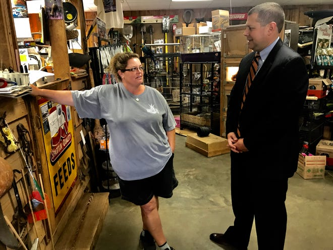 Lucas Marchant, a petition candidate for 13th Circuit Solicitor, talks with voter Leah Beacham inside her family's store, Travelers Rest Feed & Seed.