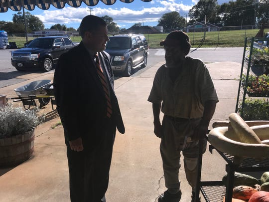 Lucas Marchant, a petition candidate for 13th Circuit Solicitor, talks with voter Benny Thompson outside Brown Feed and Seed Store in Travelers Rest.