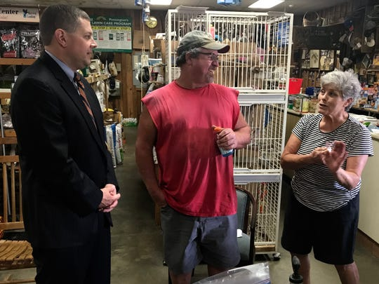 Lucas Marchant, a petition candidate for 13th Circuit Solicitor, talks with Gene Beachan and Judy Clark inside their family's store, Travelers Rest Feed & Seed.