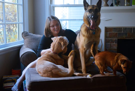 Teresa Appelwick sits with Wayway, left, Ciri, center, and her dog Tobias.  Appelwick is a volunteer with Dogs on Deployment, a national organization that links military members on deployment with dog sitters, and has taken care of Wayway and Ciri for the past 8 months while their owner is deployed.