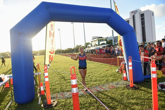 St. John's School competitor Jenna Han crosses the finish line as the IIAAG Girls Cross-Country All Island Championship first place finisher at Ramsey Field, Oct. 12, 2018.