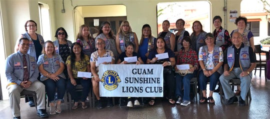 """The Guam Sunshine Lions Club, whose primary service mission is """"Caring for the Sick and the Elderly,"""" presented financial donations to five patients seeking medical treatment, on October 15 at the Chamorro Village in Hagatna.  Seated from left: Lion Frank Aguon, Jr., Lion Julie Cruz;  Dorothy Taitingfong (accepted donation for Juan Taitingfong, 64);  Dolores Cruz (accepted donation for Michael Ichihara, 48); Margaret Cabrera,66 (recipient); Jennifer Delgado (accepted donation for Juan Castro, 61); Carolina Cortez, 71 (recipient); Lion Annie Artero, and Lion Pres. Pete Babauta. Standing from left: Lions Doris Limtiaco, Connie Rivera, Clarice Quichocho, Lorraine Rivera, Sophie Losongco, Lou Jean Borja, Tish Tano, Dee Cruz, Flo Terlaje, Marietta Camacho, and Clare Cruz."""