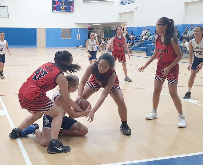 Spartans defenders Caitlyn Murphy and Tiffany Laniog trap Eagles Annabel Taylor for a jump ball call in a IIAAG Middle School Girls Basketball game at Harvest Christian Academy.