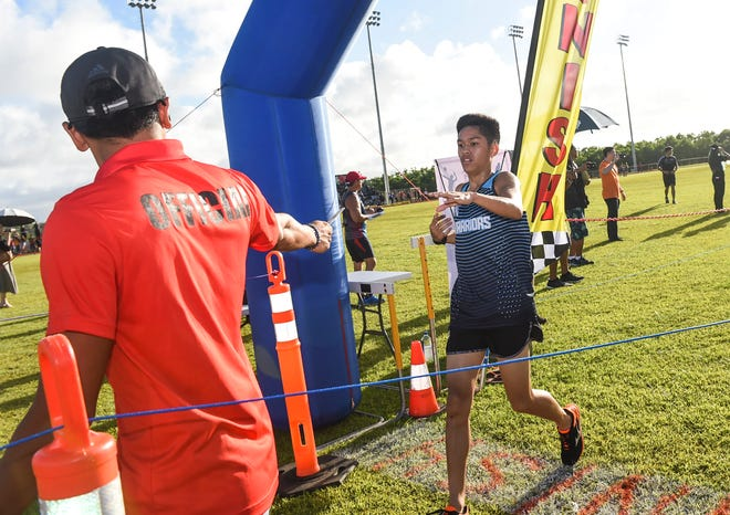 St. Paul Christian School junior Brandon Miranda finishes first during the IIAAG Boys Cross-Country All Island Championship at Ramsey Field, Oct. 12, 2018.
