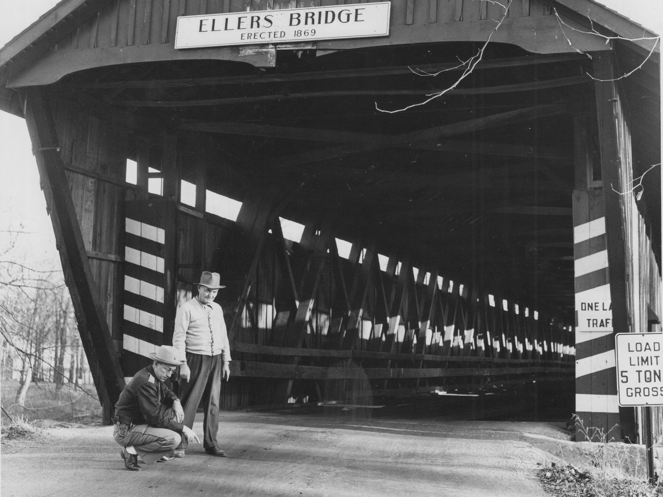 Hamilton County investigators look at traces of gasoline spread at the entrance of the Ellers covered bridge that carried 116th Street over White River in 1953 A passing motorist extinguished the flames before they had damaged the span. Arsonist were successful when it was destroyed in 1957.