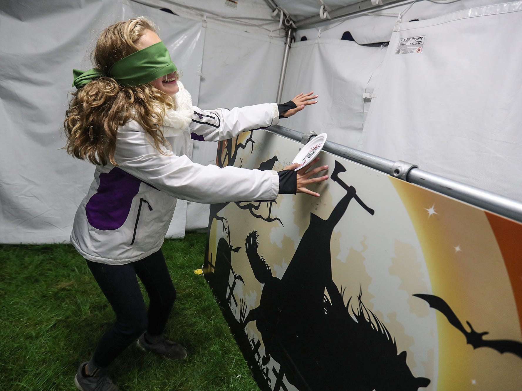 """Sydney Rohls, 11, laughs as she tries to """"pin the head on the horseman"""" on opening night of the annual Headless Horseman Halloween festival at Conner Prairie in Fishers, Ind., Thursday, Oct. 11, 2018. The festival is held from 6 to 9 p.m. every Thursday through Sunday, ending Oct. 28, 2018."""
