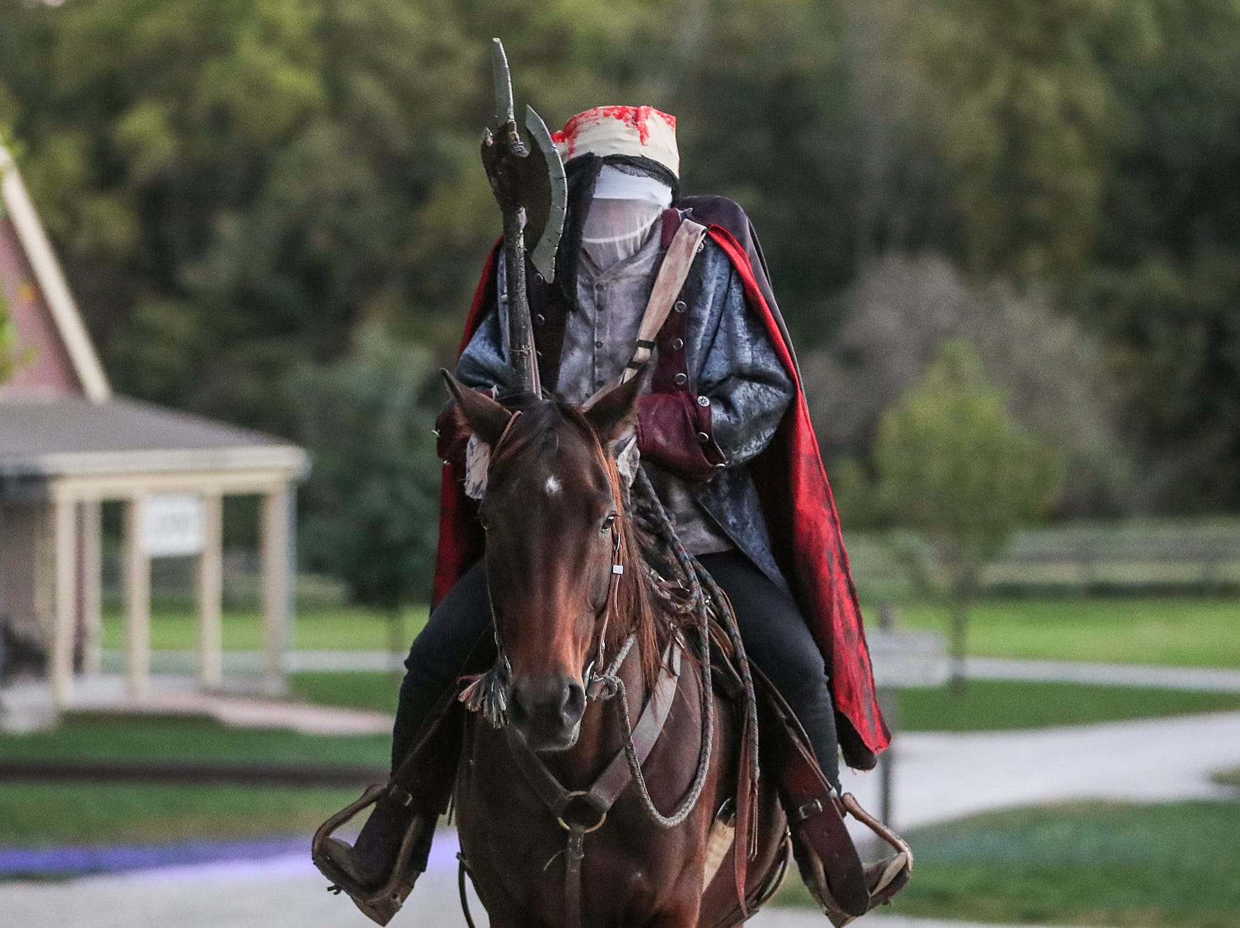 The Headless Horseman chases behind a wagon full of thrill-seekers on opening night of the annual Headless Horseman Halloween festival at Conner Prairie in Fishers, Ind., Thursday, Oct. 11, 2018. The festival is held from 6 to 9 p.m. every Thursday through Sunday, ending Oct. 28, 2018.
