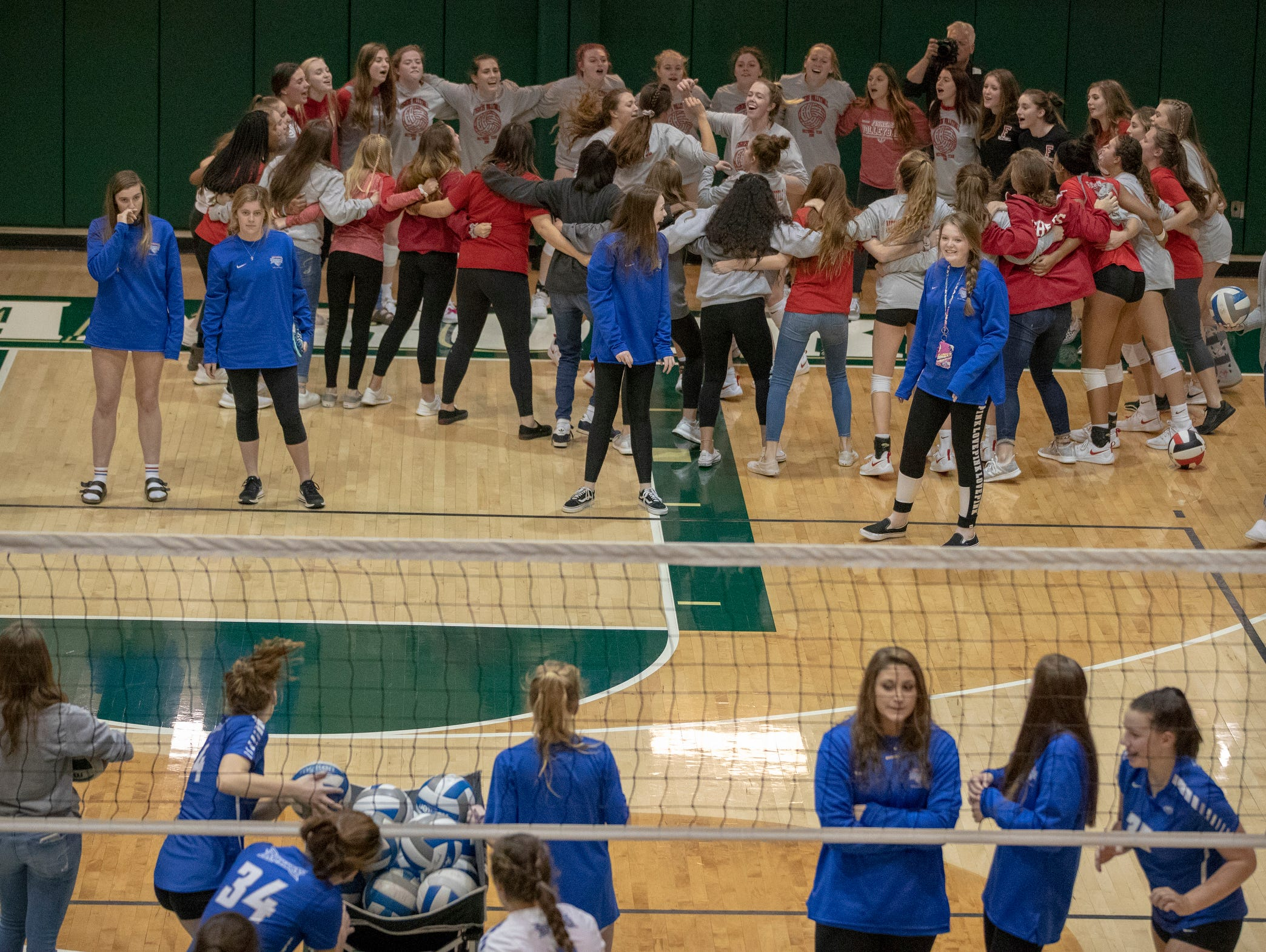 Fishers High School volleyball players cheer pregame, as Hamilton Southeastern High School warms up, before FHS defeated HSE in the first round of the sectional at Westfield High School, Westfield, Thursday, Oct. 11, 2018. The win matches them up with Westfield High School for a game on Saturday morning at 11a.m.