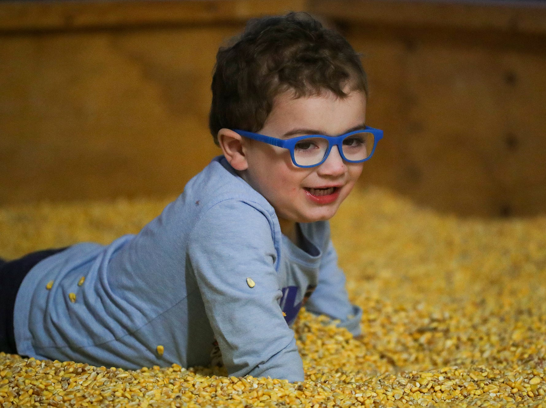 Max Carter, 3, rolls around in a large pen filled with corn kernels on opening night of the annual Headless Horseman Halloween festival at Conner Prairie in Fishers, Ind., Thursday, Oct. 11, 2018. The festival is held from 6 to 9 p.m. every Thursday through Sunday, ending Oct. 28, 2018.