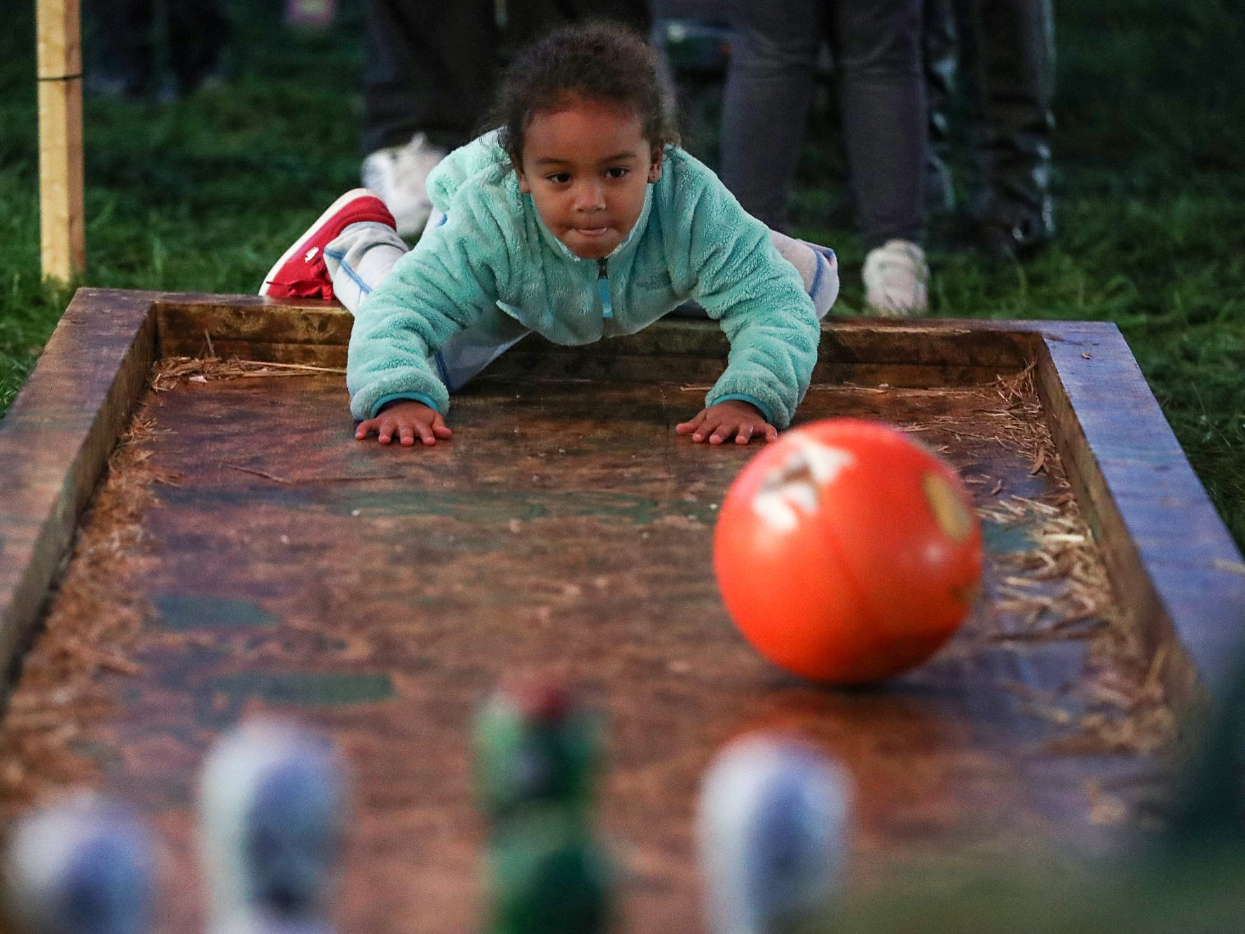 Skylar Johnson, 5, hoists a bowling ball toward pins on opening night of the annual Headless Horseman Halloween festival at Conner Prairie in Fishers, Ind., Thursday, Oct. 11, 2018. The festival is held from 6 to 9 p.m. every Thursday through Sunday, ending Oct. 28, 2018.