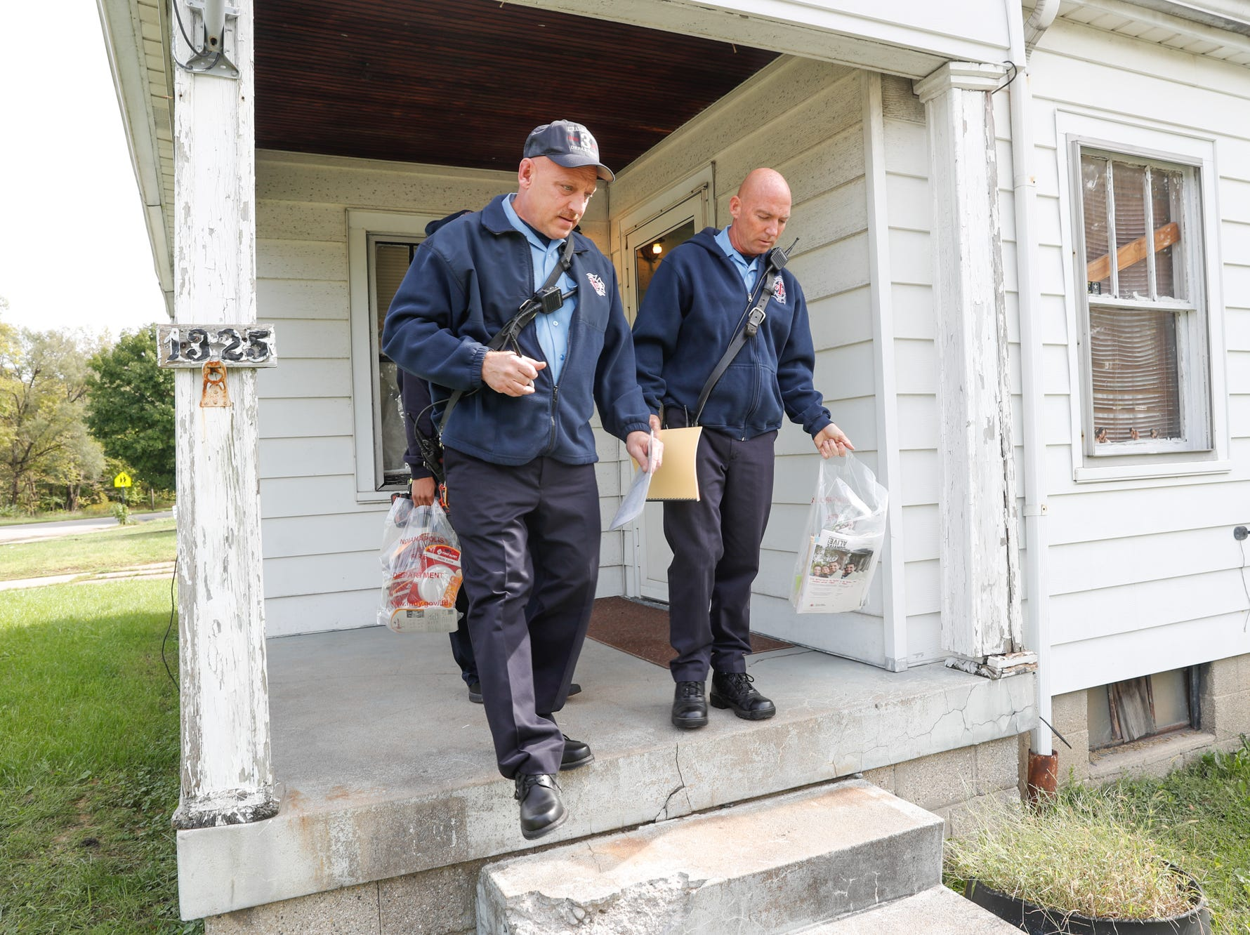 IFD Firefighter Paul Lambert, left, and IFD Firefighter Tim Rumple, right, go door to door delivering safety materials including smoke alarms during IFD's home safety blitz in Indianapolis for National Fire Prevention Week, on Friday, October 12, 2018. IFD chose the area around IFD Station 15 which experienced 9 residential fires in 2018 for the blitz.