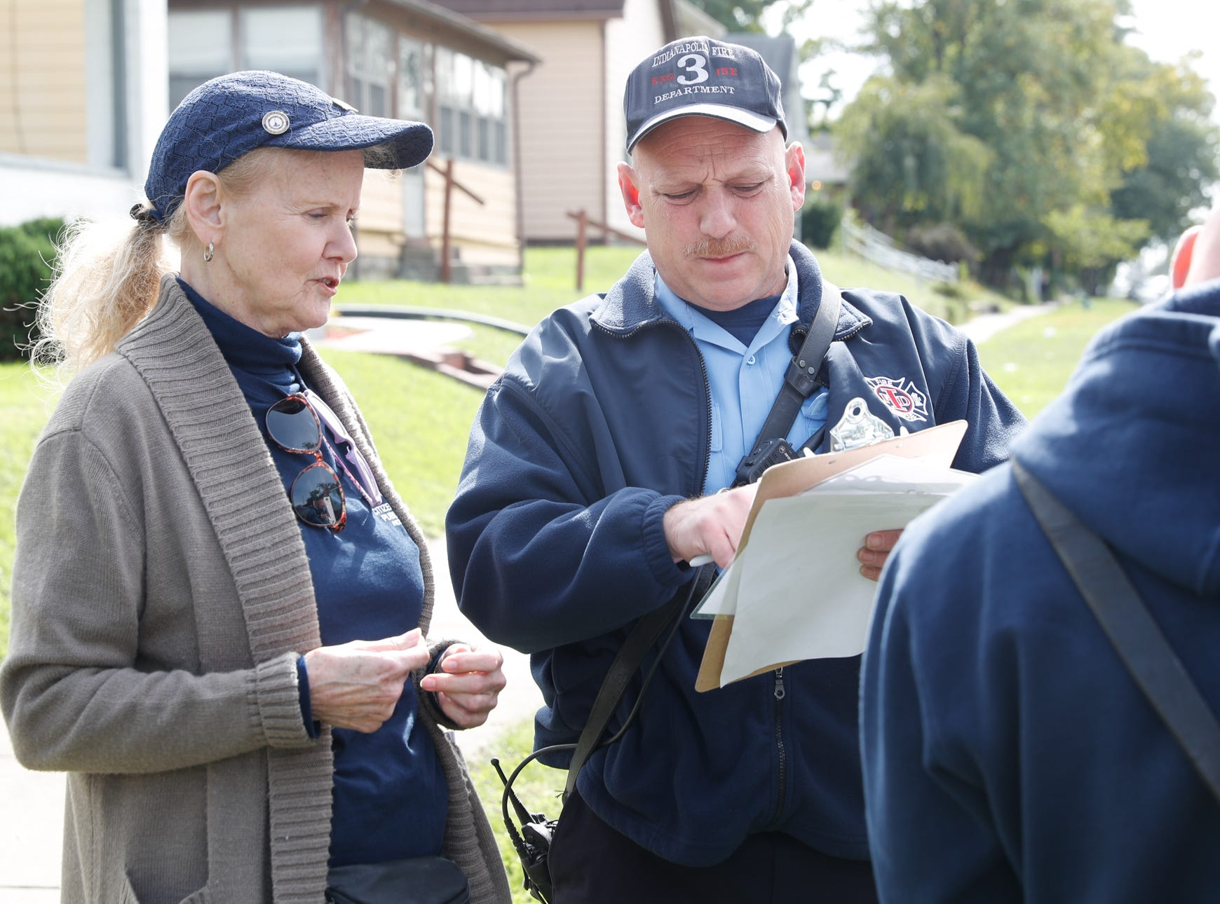 Volunteer Lana Stevens, left, with the Citizens Alliance for Public Safety,  and Firefighter Paul Lambert , center, go door to door delivering safety materials including smoke alarms during IFD's home safety blitz in Indianapolis for National Fire Prevention Week, on Friday, October 12, 2018. IFD chose the area around IFD Station 15 which experienced 9 residential fires in 2018 for the blitz.