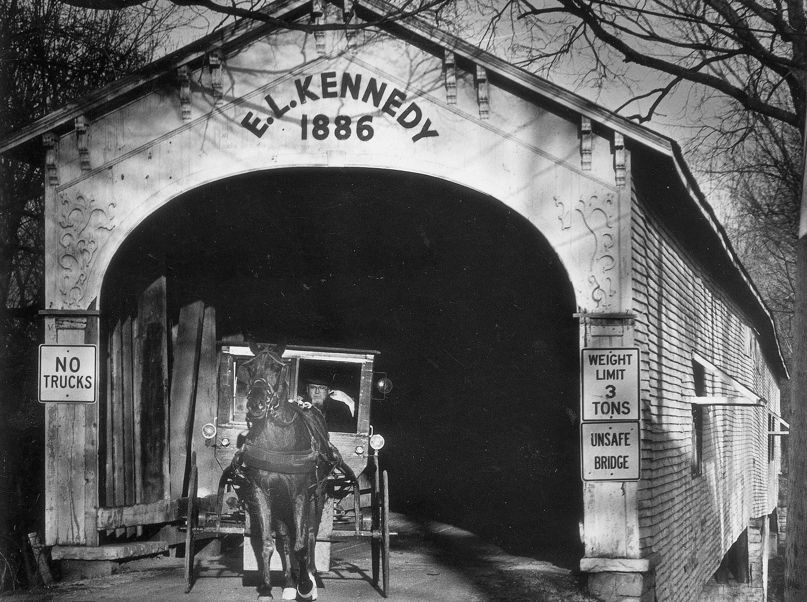 An Amish-driven horse and buggy pass through the historic E.L. Kennedy covered bridge in Moscow in Rush County in 1986.