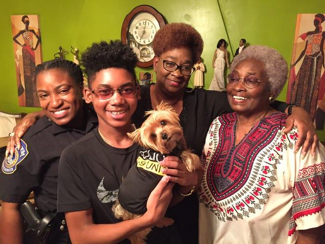 DuJuan Jones, center, holds the family police pup. From left: IMPD Officer Samone Willis, Rhonda Byrd and Doris Byrd.