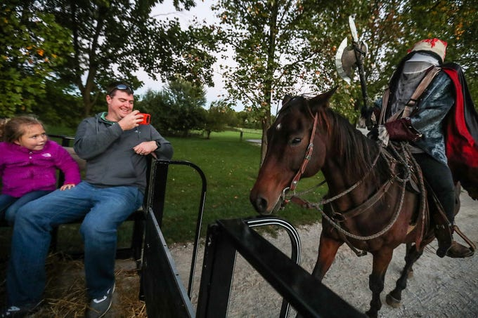 From left, Ava Rinehart, 4, and her father Morgan Rinehart watch as the Headless Horseman chases close behind their wagon on opening night of the annual Headless Horseman Halloween festival at Conner Prairie in Fishers, Ind., Thursday, Oct. 11, 2018. The festival is held from 6 to 9 p.m. every Thursday through Sunday, ending Oct. 28, 2018.