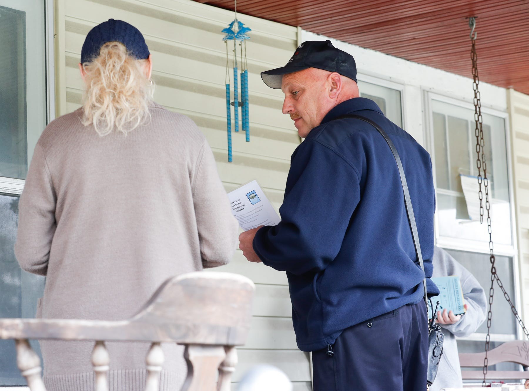Volunteer Lana Stevens, left, with the Citizens Alliance for Public Safety,  and Firefighter Paul Lambert , center, speak to a citizen about fire prevention as they go door to door delivering safety materials including smoke alarms during IFD's home safety blitz in Indianapolis for National Fire Prevention Week, on Friday, October 12, 2018. IFD chose the area around IFD Station 15 which experienced 9 residential fires in 2018 for the blitz.
