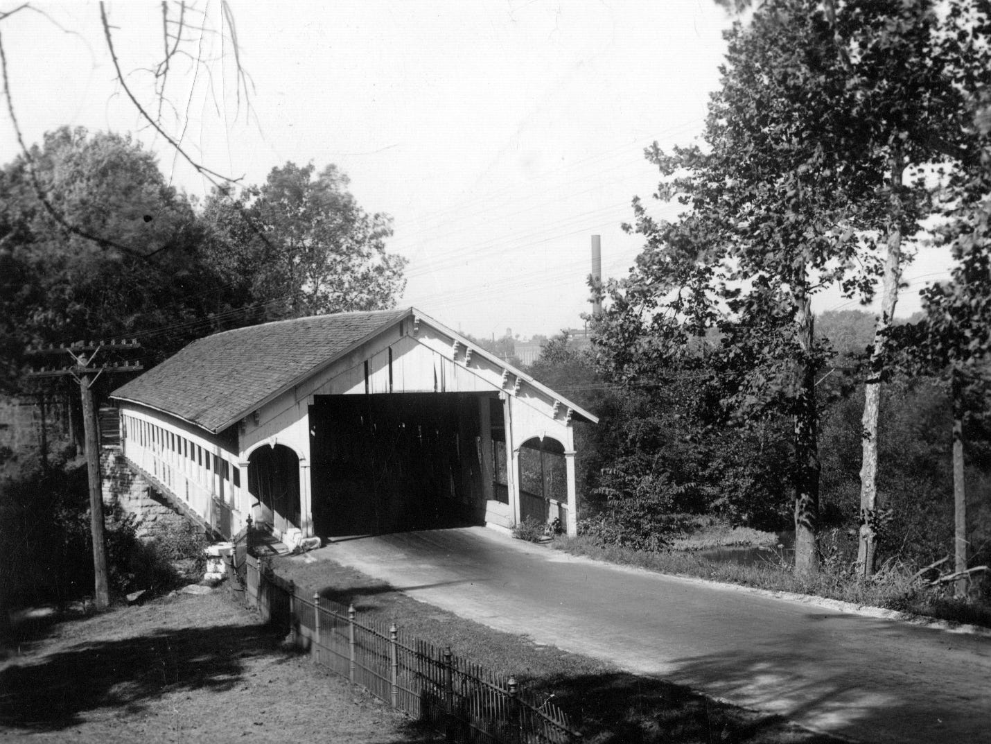 Single-span wooden bridge over Flat Rock Creek on S.R. 44 near Rushville in 1933. Pedestrian walkways are on both sides of the bridge.