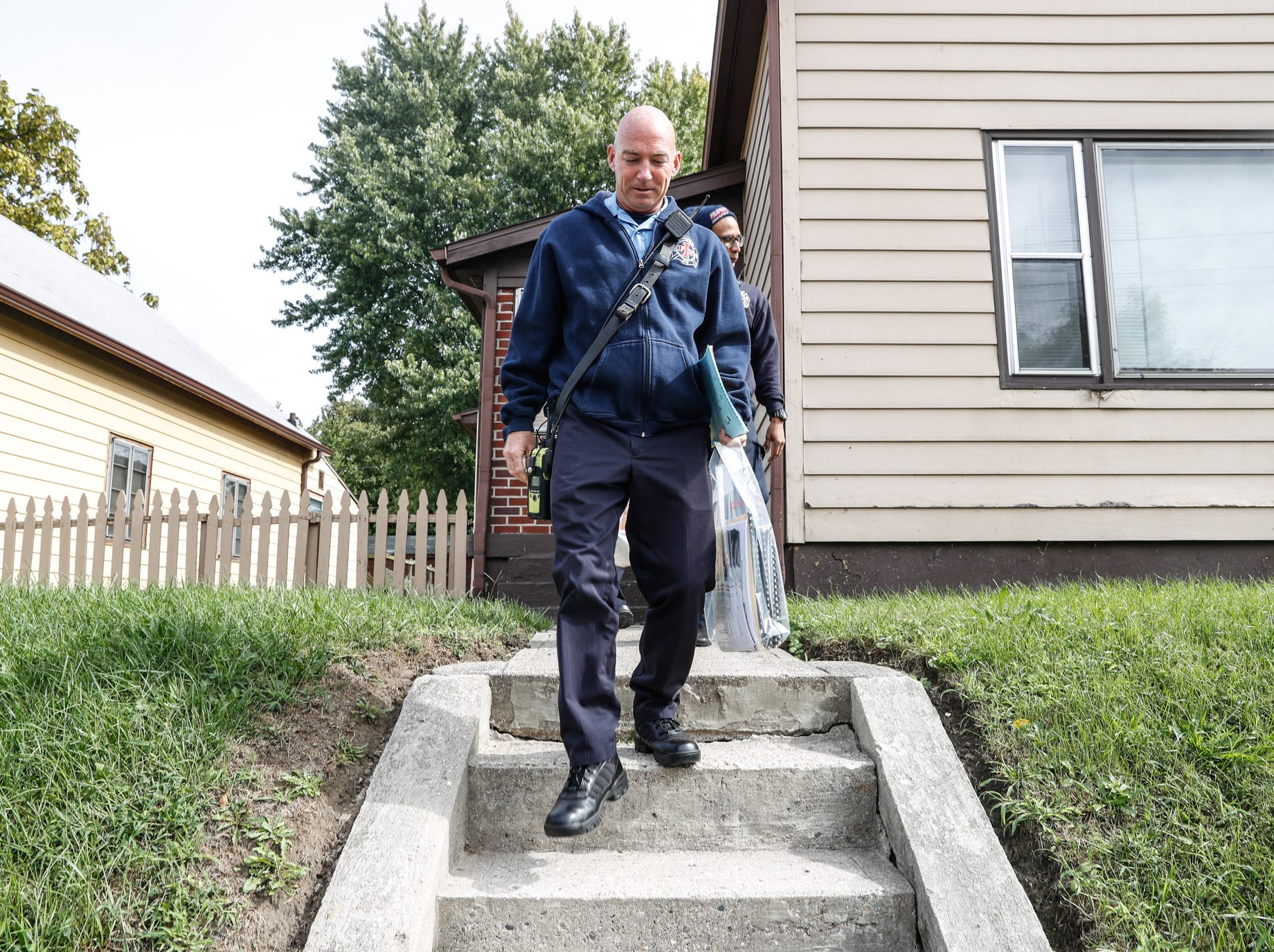 IFD Firefighters Tim Rumple, front, and Donovan Abernathy, right, go door to door delivering safety materials including smoke alarms during IFD's home safety blitz in Indianapolis for National Fire Prevention Week, on Friday, October 12, 2018. IFD chose the area around IFD Station 15 which experienced 9 residential fires in 2018 for the blitz.