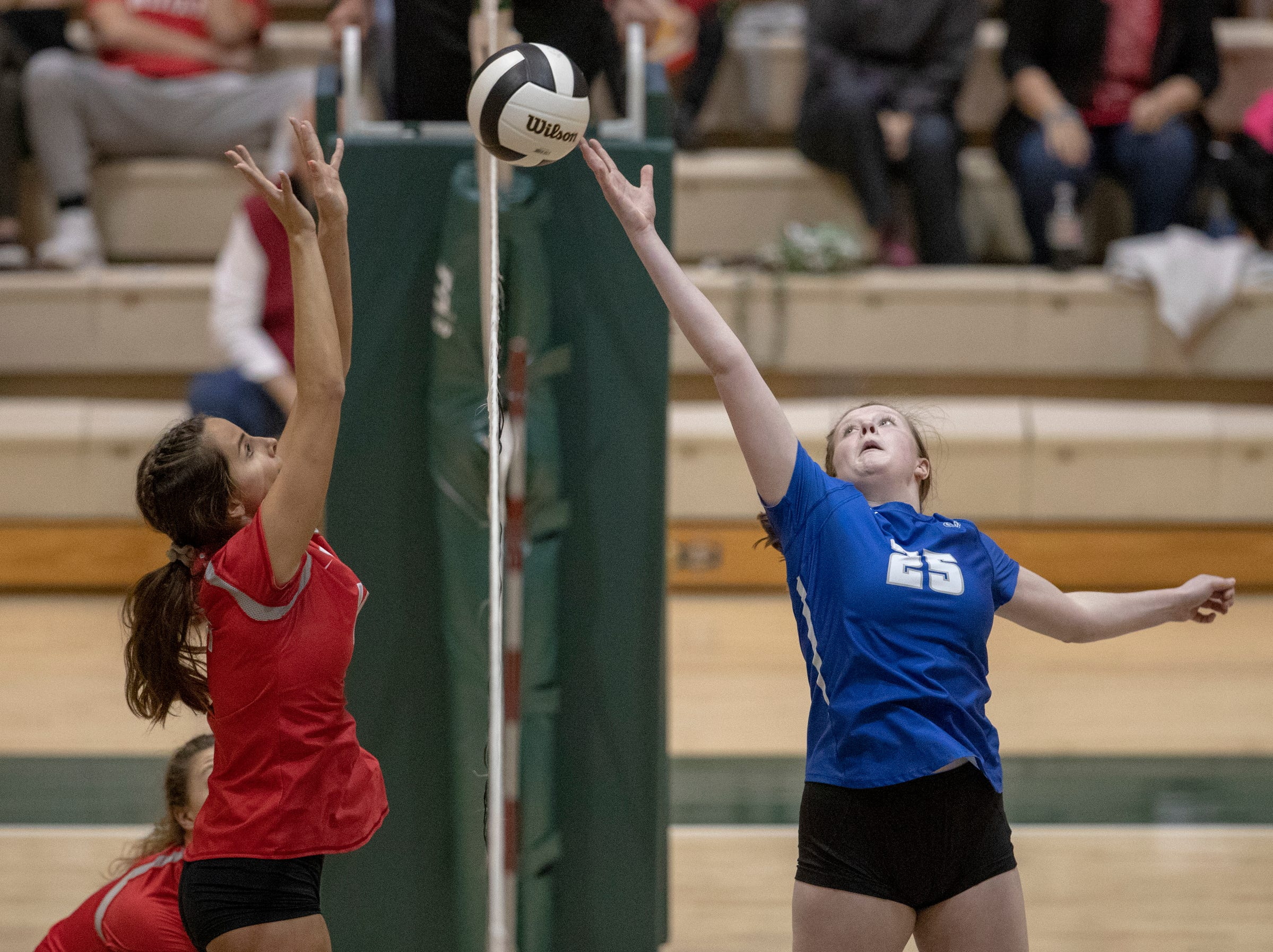 Olivia Phillips (right) of Hamilton Southeastern High School tries to sneak a ball past Fishers High School defenders in three straight sets in the first round of the volleyball sectional at Westfield High School, Westfield, Thursday, Oct. 11, 2018. The win matches them up with Westfield High School for a game on Saturday morning at 11a.m.