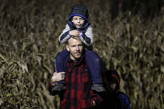 Jason Thorne and son Luke Thorne, 4, exit the corn maze on opening night of the annual Headless Horseman Halloween festival at Conner Prairie in Fishers, Ind., Thursday, Oct. 11, 2018. The festival is held from 6 to 9 p.m. every Thursday through Sunday, ending Oct. 28, 2018.