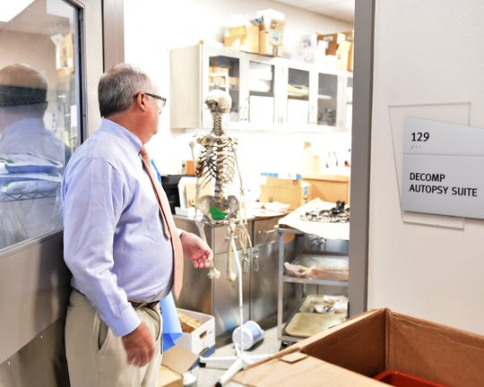 Sam Howell, director of the Mississippi Crime Lab, looks in on an autopsy suite where forensic anthropologists work on Thursday, Oct. 11, 2018.