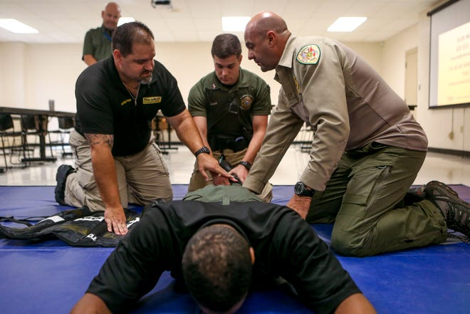 """Scott Woods, left, instructs David Glover, center, and V Dollahite Jr, right, while practicing using the restraining system on Derek Cannon during a training session for """"The Wrap"""" at West Tennessee Regional Training Center in Jackson, Tenn., on Friday, Oct. 12, 2018."""