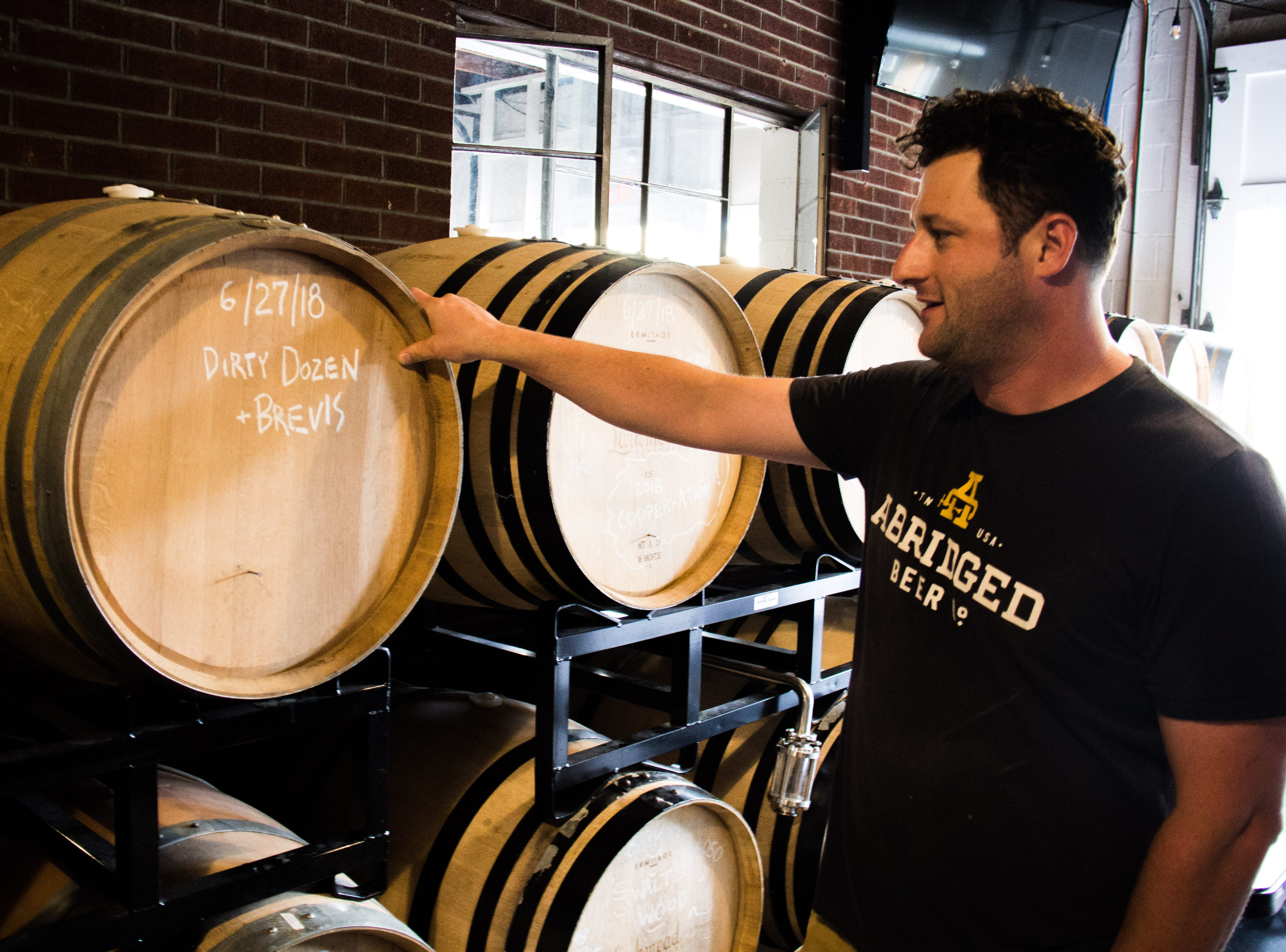 Abridged Beer Co. founder Jesse Bowers looks at a barrel of sour beer Oct. 10, 2018.