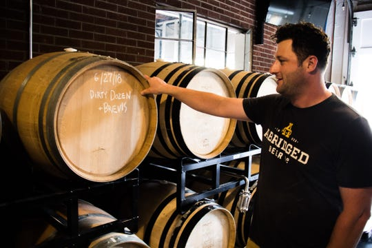 Abridged Beer Co. Founder Jesse Bowers looks at a barrel of sour beer at his current Lockett Road location on Oct. 10, 2018.