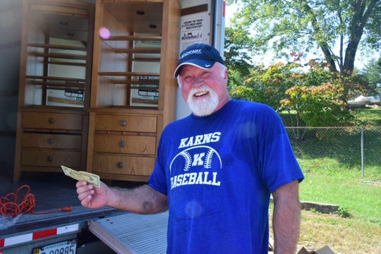 Gary Farrell sold a grill at a rummage sale held by the Karns High School Baseball Boosters at the Lions Club parking lot Saturday, Oct. 6.
