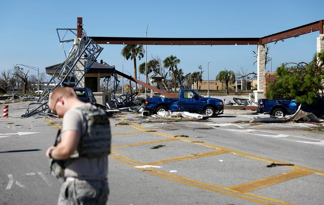 A soldier stands guard at the damaged entrance to Tyndall Air Force Base in Panama City, Fla., Thursday, Oct. 11, 2018, in the aftermath of hurricane Michael. The devastation inflicted by Hurricane Michael came into focus Thursday with rows upon rows of homes found smashed to pieces, and rescue crews began making their way into the stricken areas in hopes of accounting for hundreds of people who may have stayed behind.