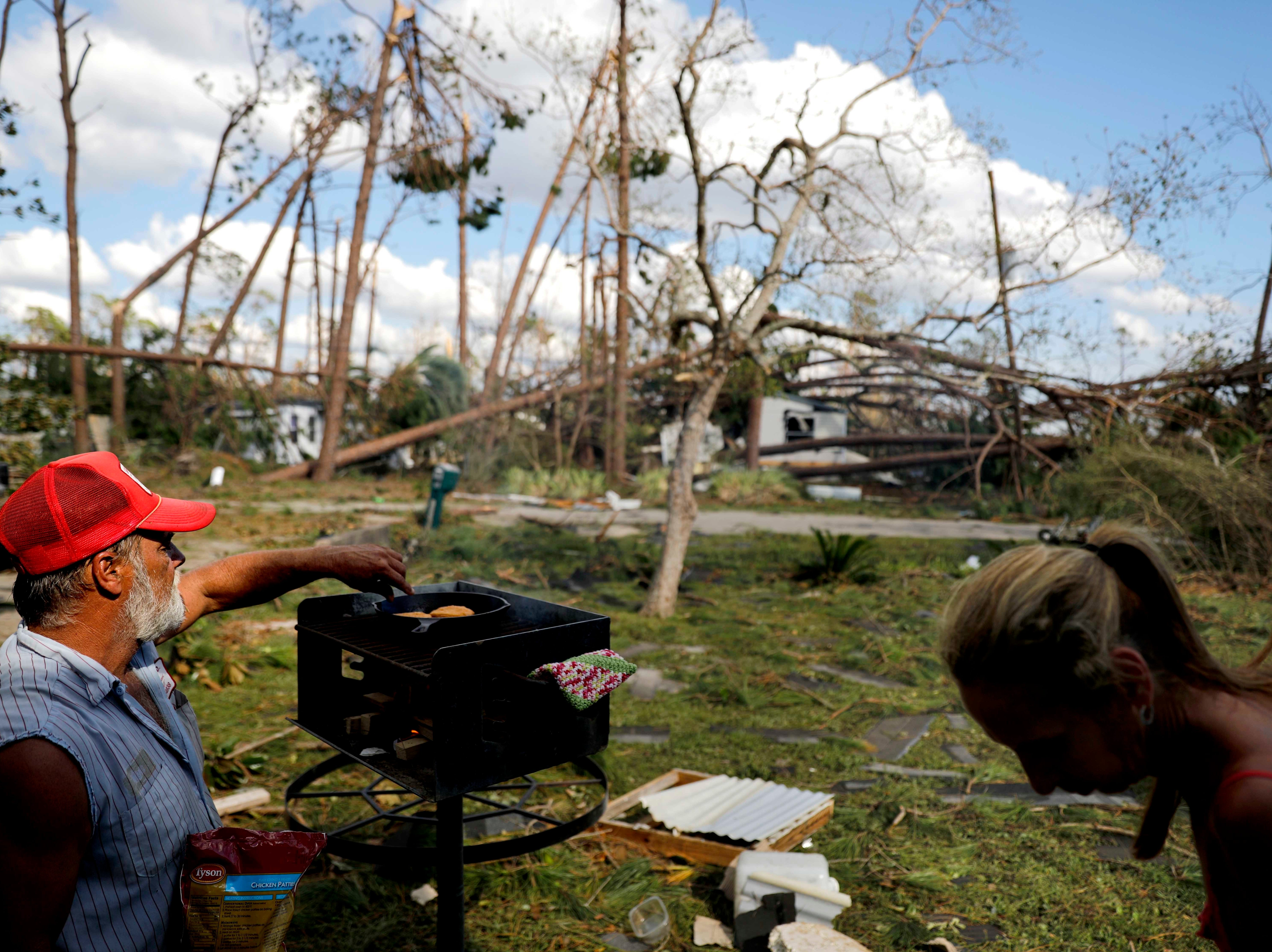 Monica, right, and Kevin Jones cook chicken on an open flame in their front yard as homes in the background are damaged by fallen trees from hurricane Michael in Callaway, Fla., Thursday, Oct. 11, 2018.
