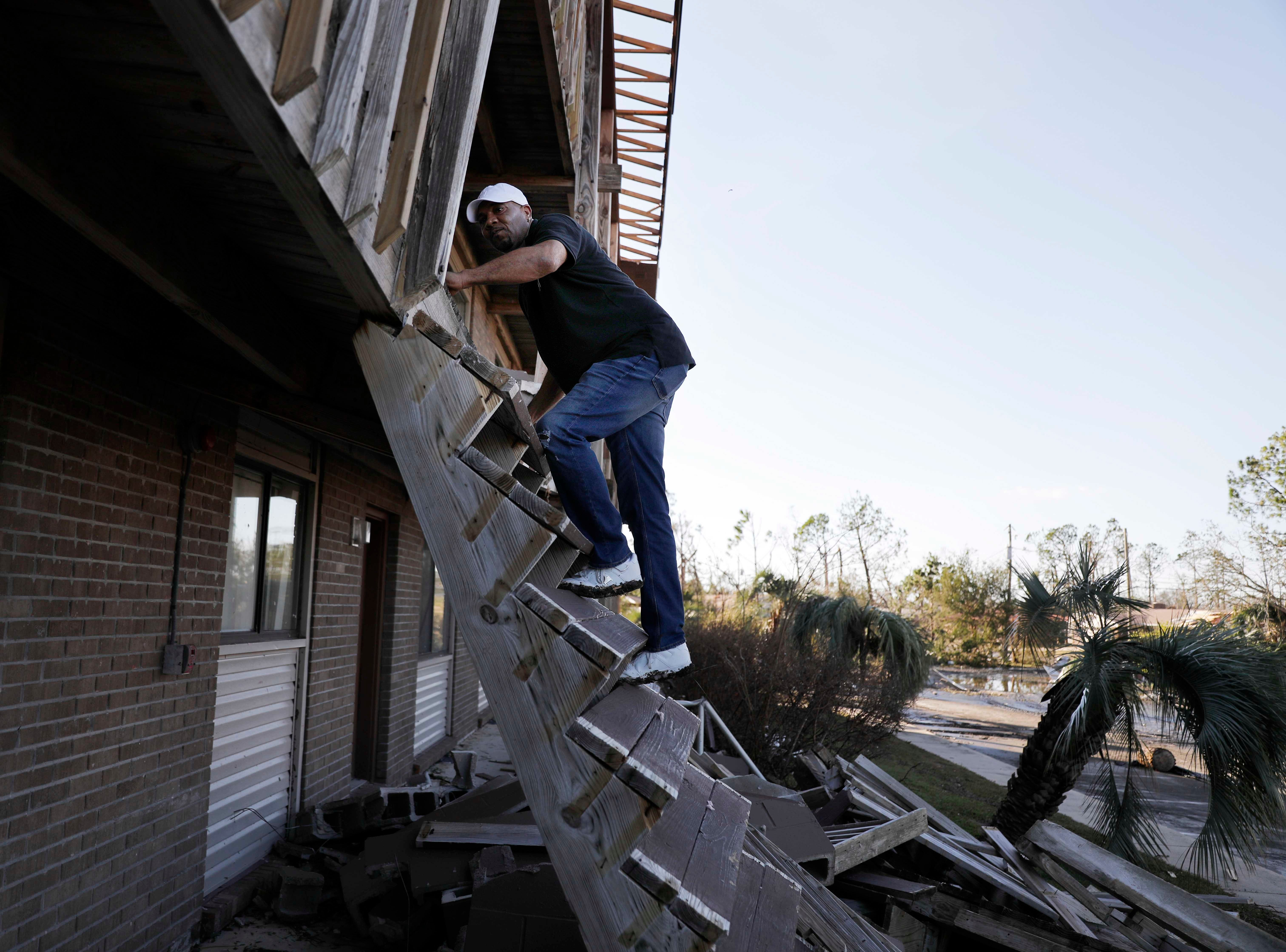 David Blackston climbs a damaged stairway to check on his second floor apartment in the aftermath of hurricane Michael in Callaway, Fla., Thursday, Oct. 11, 2018. Blackston and his wife evacuated to a hotel in Alabama on Monday ahead of the storm.