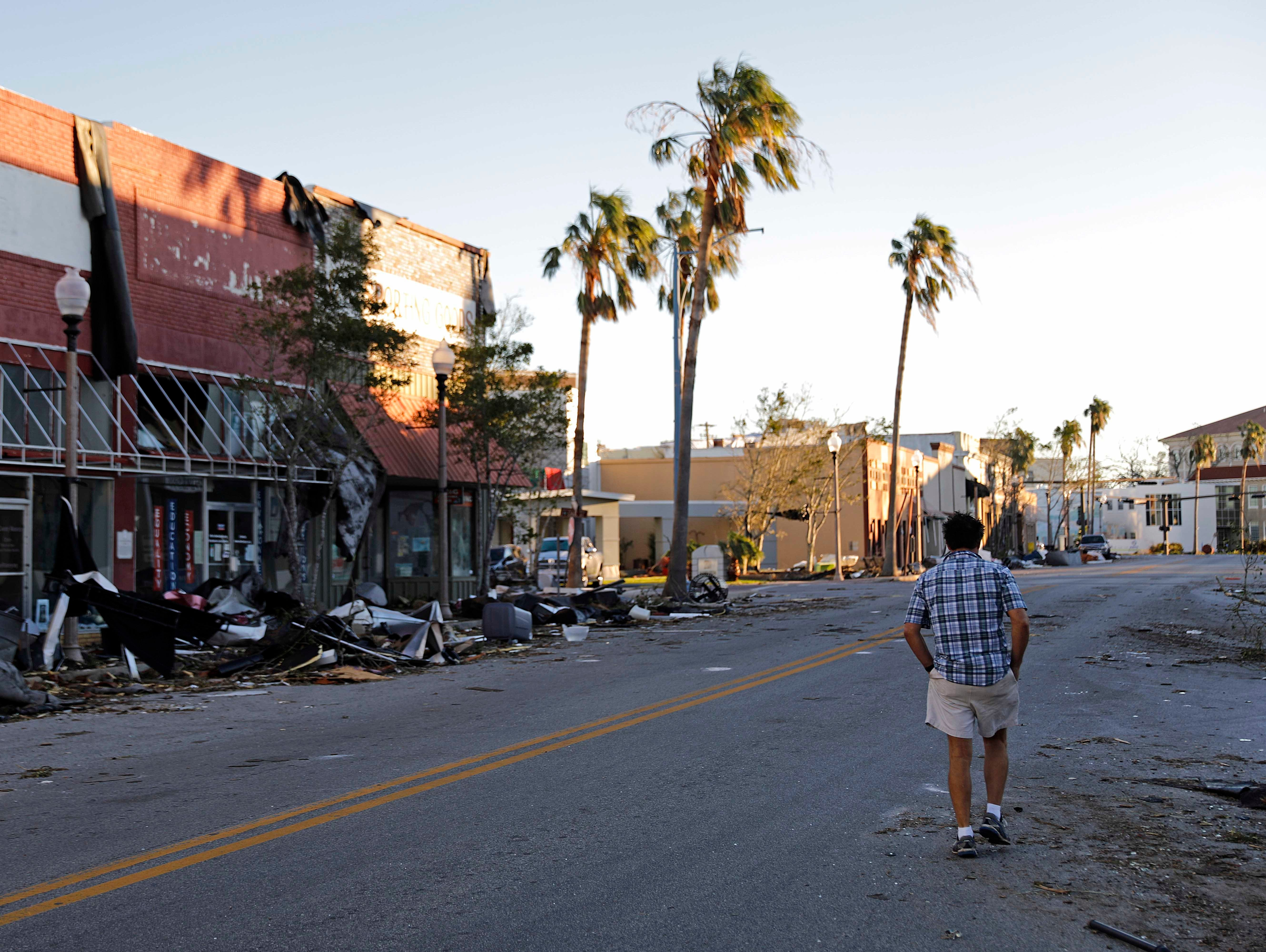 A man walks through the damaged historical downtown district in the aftermath of Hurricane Michael in Panama City, Fla., Friday, Oct. 12, 2018.