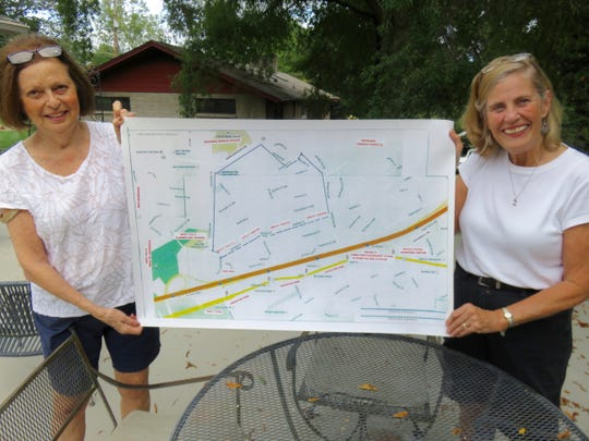 Sandy Robinson, left, and Anne Crais hold up a sidewalk map used in recent months to help get support for a sidewalk on Sheffield Drive.