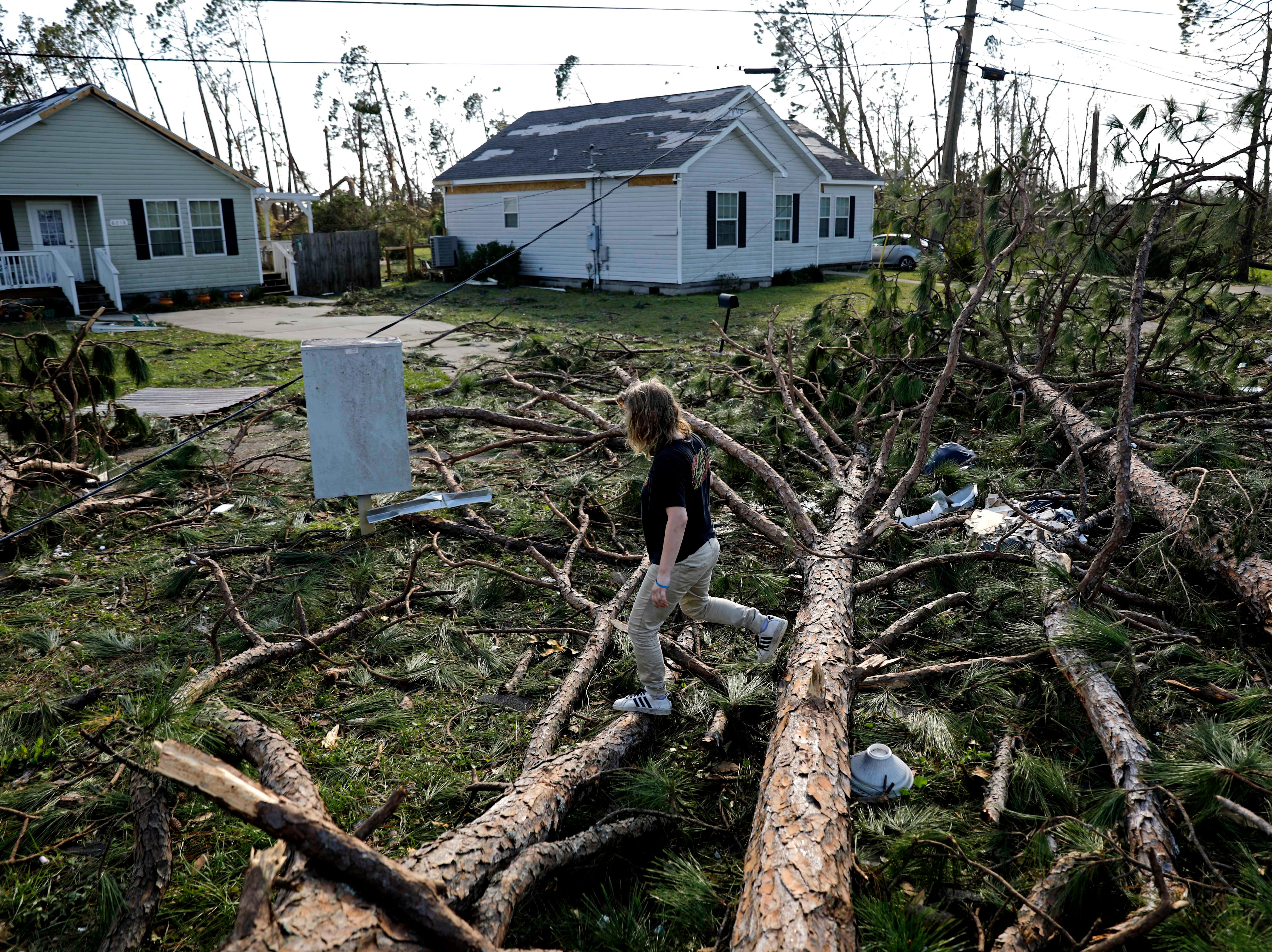 Kelsey Gronbeck walks over fallen trees blocking a street to check on a friend's house in the aftermath of hurricane Michael in Callaway, Fla., Thursday, Oct. 11, 2018.