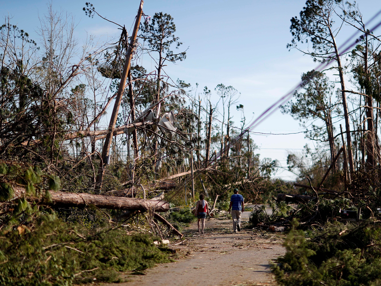 Pedestrians walk through a damaged neighborhood in the aftermath of hurricane Michael in Callaway, Fla., Thursday, Oct. 11, 2018.