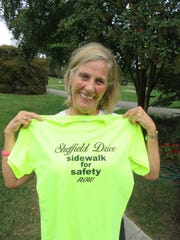 Anne Crais holds up a T-shirt given out during neighborhood walks to draw support for the Sheffield sidewalk project.